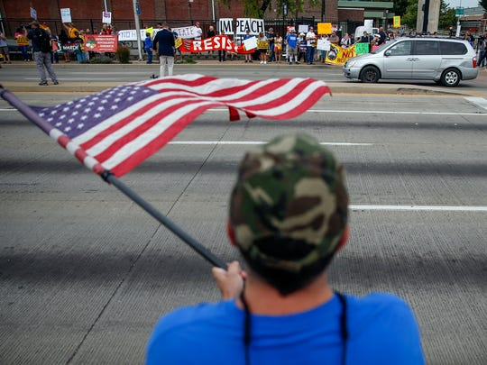 Bret David, a President Trump supporter, stands across 38th Street as protesters rally against Trump's visit and speech in Indianapolis.
