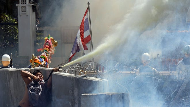 A Thai demonstrator sprays smoke on police during clashes in Bangkok, as protesters try to storm the government headquarters of Prime Minister Yingluck Shinawatra.