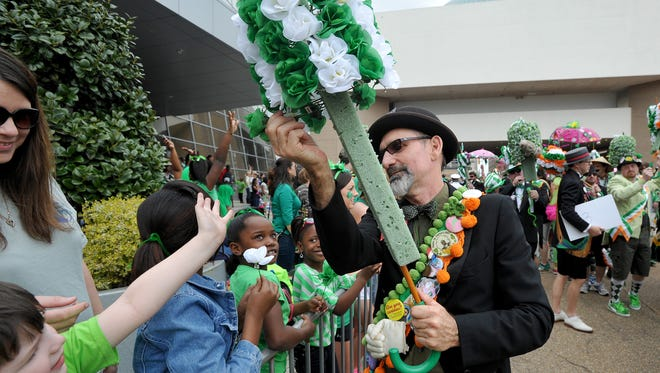 Malcolm White hands out flowers to people along Lamar Street as he leads the Mal's St. Paddy's Parade in downtown Jackson Saturday.