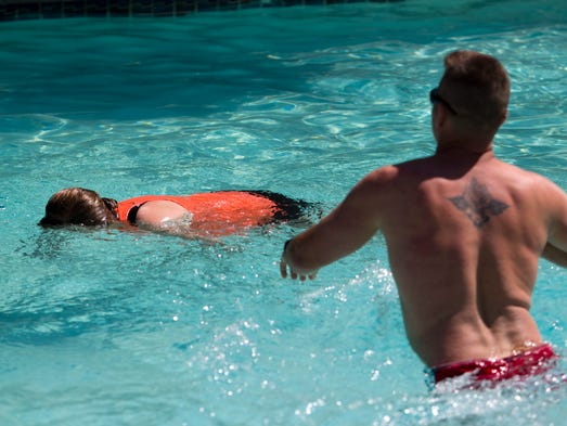 Juston  Doherty, a Phoenix firefighter, tends to Mackenzie Tardiff, a Phoenix fire cadet playing a drowning victim, during a mock drowning and pool rescue at the Hole-in-the-Wall River Ranch at the Pointe Hilton Squaw Peak Resort in Phoenix on Tuesday, April 1, 2014.
