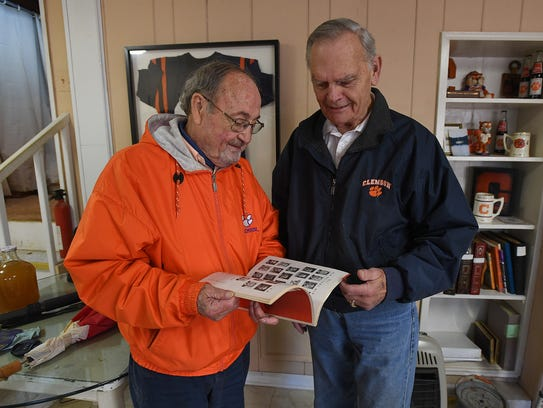 """1958 Clemson Sugar Bowl team members George """"Pogo"""" Usry, left, who was a junior tailback, and Harold Olson, who was a junior right offensive tackle, look through a 1958 Sugar Bowl game program at Usry's home in Clemson."""