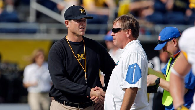 Jan 1, 2016; Orlando, FL, USA; Michigan Wolverines head coach Jim Harbaugh (left) and Florida Gators head coach Jim McElwain meet at midfield before the 2016 Citrus Bowl at Orlando Citrus Bowl Stadium.