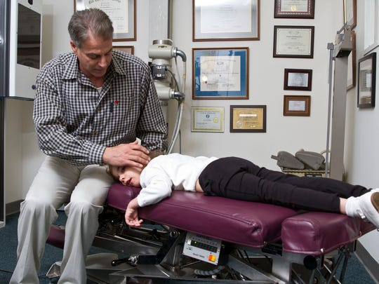 Dr. Steven Pollack of Pollack Health and Wellness Center in Beachwood gives an adjustment to patient Vienna Zucaro, 6 of Toms River.