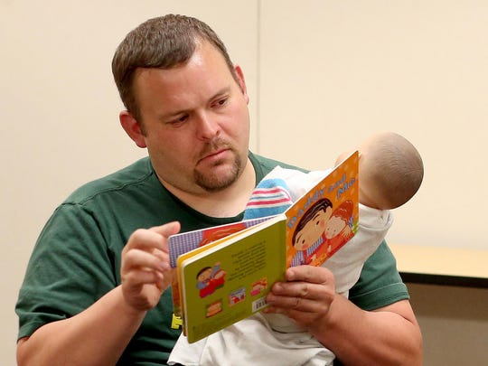 Greg Bakanoff, of McMinnville, looks through a children's book while holding a doll during the Boot Camp for New Dads on Monday, June 15, at Salem Hospital. Bakanoff has a son who was born in earlier in the month.