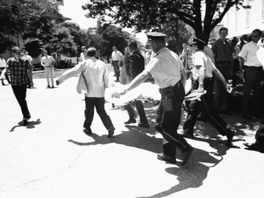 One of the victims of Charles Whitman, a sniper who gunned down students from a perch in the University of Texas tower, is carried across campus Aug. 1, 1966, in Austin, Texas, to a waiting ambulance.