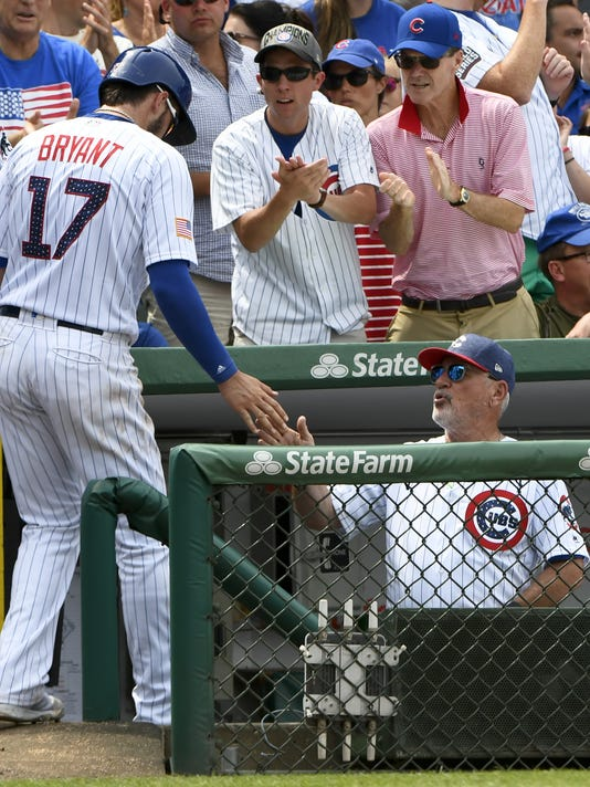Chicago Cubs Kris Bryant (17) high fives Chicago Cubs manager Joe Maddon (70) after he scores during the fifth inning of a baseball game against the Tampa Bay Rays on Tuesday, July 4, 2017, in Chicago. (AP Photo/Matt Marton)