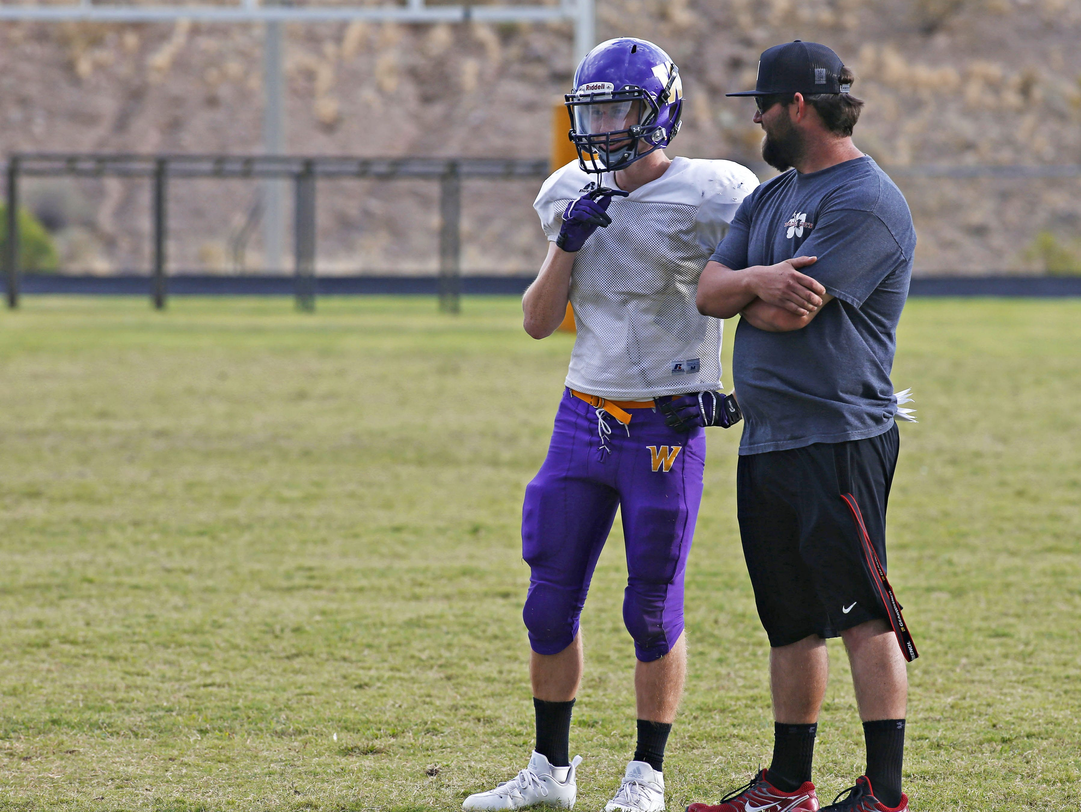 Jacob Blackburn talks with defensive line coach Cameron Shaw, right, during football practice at Wickenburg High School, where he starts at outside linebacker.