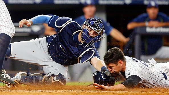 NEW YORK, NY - APRIL 22:  Curt Casali #19 of the Tampa Bay Rays is late with the tag as Jacoby Ellsbury #22 of the New York Yankees steals home during the fifth inning at Yankee Stadium on April 22, 2016 in the Bronx borough of New York City.