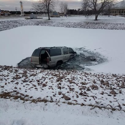A vehicle sits in a pond following a Tuesday morning