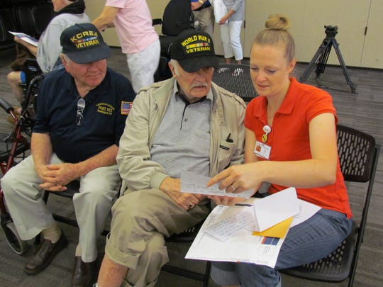 World War II veteran Ross Rohn, center, listens as Mary Ann Maher, Recreation Assistant at the Southern Utah Veterans Home in Ivins City, reads him a letter he received as part of Mail Call.