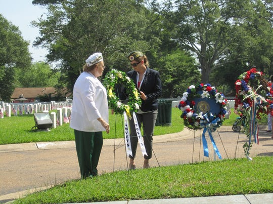 Mary Honshul (left), the first vice president of Amvets Chapter 7 in Alexandria, places a wreath Monday at the Alexandria National Cemetery with Post 7 Commander Laura McFarlain.