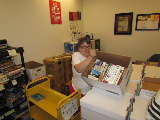 Friends of the Stayton Library's Pam Pugsley visited Canyon Conversations at Moxieberry. She stressed that volunteers are always welcome -- they can help with tasks like this one, sorting books. The group will have an Eighth Anniversary celebration Aug. 30 through Sept. 3 by holding a $1 store-wide sale, 349 N. 3rd Ave., Stayton.