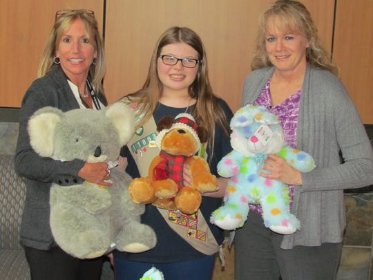 """Ashlee Ellis, an 8th-grade student at Whiteaker Middle School in Keizer, middle, Santiam Hospital CFO/COO Maggie Hudson, left, and Chief Nursing Officer Sherri Steele hold a few of the more than 100 """"comfort items"""" delivered to the hospital as part of Ashlee's Girl Scouts Silver Award project.  Ashlee also delivered similar items gathered to Salem Hospital's emergency room, pediatrics, Silverton Hospital and has plans to make a delivery to Dallas Hospital."""