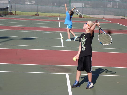 Rylee Wilson (foreground) and Emily Blake practice serving at this summer's Neighborhood Tennis Program.