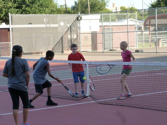 Haylee Garcia (left to right), Jamariyon Henry, Jake Lalonde and Alexis Eads play a game during the 26th annual Neighborhood Tennis Program.