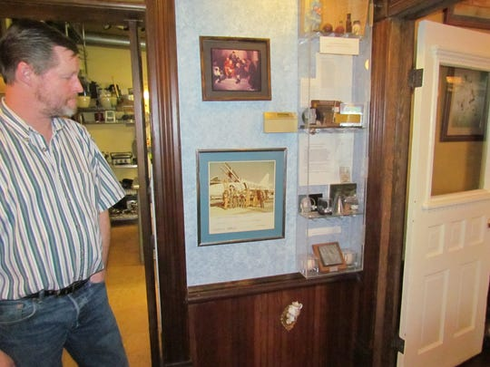 James Loftus shows the display case exhibiting a mix of Apollo mission artifacts, historical pieces found in the home and signed Houston Astros baseballs from the mid 70s  at the Gardner House Café and Bed & Breakfast on 3rd Street, Stayton, Thursday, Feb. 27, 2014.