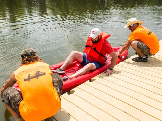 Harry Wood exits his rented kayak from Cowboy Mike's Canoe Rental after some time on the Cooper River.