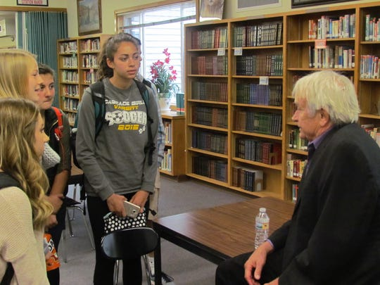 Olympic middle-distance runner Dyrol Burleson, a Turner-area resident and inductee into the National Track & Field Hall of Fame, addresses students and visitors a Cascade High School's library Thursday, Oct. 19.