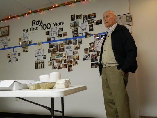 Ray Narouth stands next to the timeline of his life at the 100-year-old bartender's birthday party at the Gold Slipper in December 2011 in Dunlap, Ia.