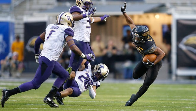 Southern Miss running back Ito Smith is tripped up by Washington defenders in the third quarter on Saturday. The Golden Eagles lost to the Huskies 44-31 in the Heart of Dallas Bowl.