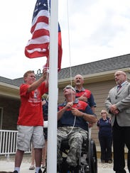 Former Army Staff Sgt. Stephen Valyou, center left,