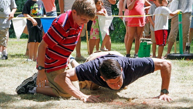 Sam Ryan watches his dad, Congressman Paul Ryan, to try to get his frog to jump during a frog-jumping competition at a previous Duusman Derby Days.