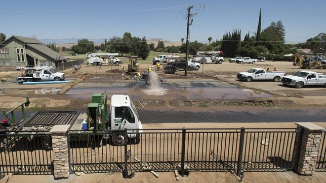 Crews work to repair a broken water main along Belmont Road just south of Visalia Road in Exeter on Monday. The rupture caused by Southern California Edison crews working in the area left most parts of Exeter without water.