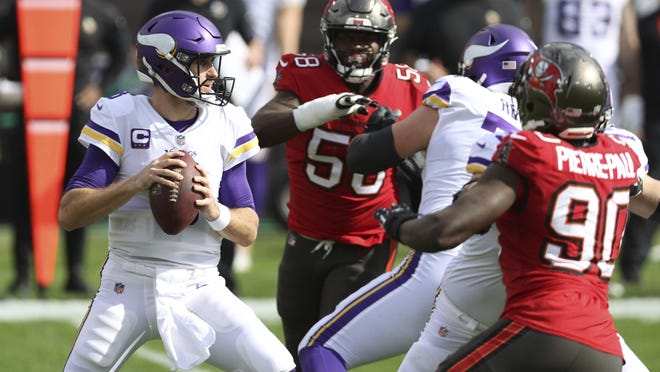 Minnesota Vikings quarterback Kirk Cousins (8) looks for a receiver as he is pressured by Tampa Bay Buccaneers outside linebacker Shaquil Barrett (58) and outside linebacker Jason Pierre-Paul (90) during the first half of an NFL football game Sunday, Dec. 13, 2020, in Tampa, Fla.