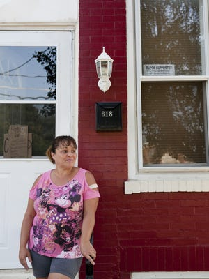 Marizga Cordero stands on her front steps at West and Royden streets in Camden. Residents of the Lanning Square section of Camden have been taking back by the community and continue to keep the area clean after resident Pino Rodriguez rallied neighborhood.