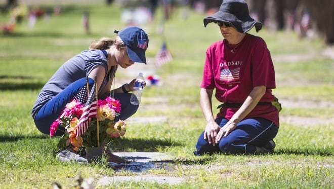 Alexandria Ellsworth, 21, left, Mesa, and her mother, Susan Freeman Ellsworth, visit the grave of Susan's mother and father, Alexandria's grandparents, at the Mesa Memorial Cemetery on Memorial Day, Monday, May 28, 2018. Susan's father was a veteran of the Korean War.