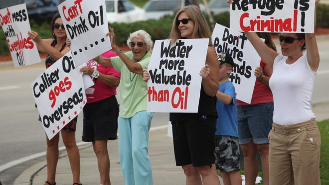 Kimberly Duran, right, Marlene Robinson, second from right, and others protest proposed oil drilling in the Golden Gate area.   Jack Hardman/The News-Press Kimberly Duran, right, and Marlene Robinson, 2nd from right, along with other protestors, receive support for their cause by passing motorists during a protest near Barron Collier Company headquarters last week.