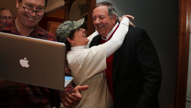 Ted Crozier Jr. and his wife, Ann Marie, react as Patrick Fitch shows them the election results. Crozier beat out two fellow Republicans to win the GOP nomination for Circuit Court judge Part III, by a large margin Tuesday night.
