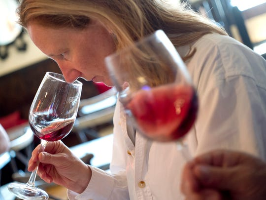 Lori Delia samples a bottle of Pinot Nero during recent tasting to pick the labels to offer.