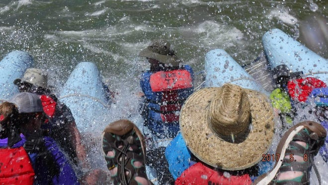 A travel group rafts down the Colorado River through the Grand Canyon.