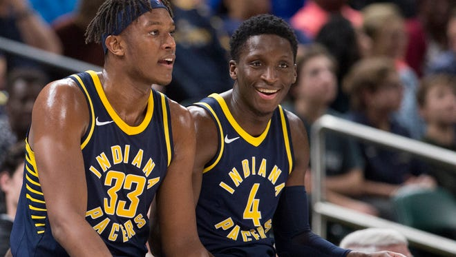 Myles Turner (left), and Indiana teammate Victor Oladipo chat at the scorers table during a break, Orlando Magic at Indiana Pacers, Bankers Life Fieldhouse, Indianapolis, Monday, Nov. 27, 2017. Indiana won 121-109.