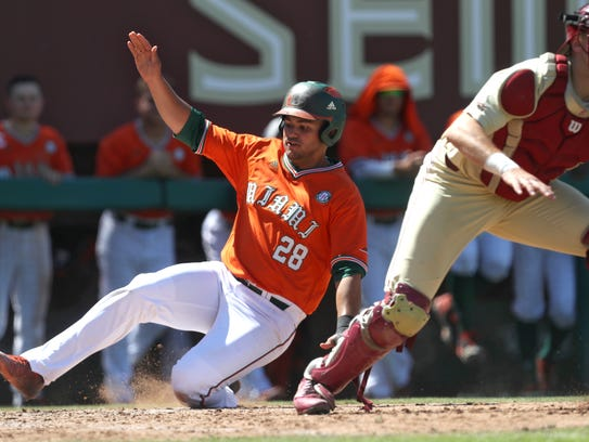 Miami's Ray Gil slides in safely at home plate for