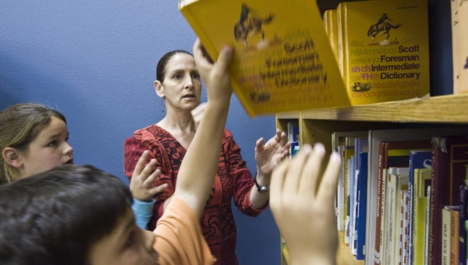 Desert Trails Elementary School librarian Nancy Taub makes sure all the dictionaries are replaced on the shelf after guiding 3rd graders through dictionary skills exercises.