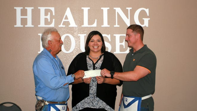 Roger Morris, left, and Rocky Wyrembelski presented a check for $1,000 to The Healing House of Deming. The Deming Masonic Lodge partnered with the Masonic Charity Foundation of New Mexico in providing this assistance to the facility which provides help to abused men, women and children in this area. Accepting the check is Irene Trejo, manager.