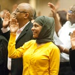 Farzana Hussain, of Bangladesh, center, yellow, takes the oath of citizenship with, about 250 other immigrants at a ceremony at the Galt House Hotel in Louisville. 29 August 2014