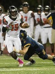 Lely quarterback Jonis Dieudonne is tackled by Andre Eaton of Naples during the game at Naples High Friday night, October 6, 2017.