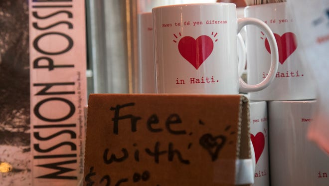 Bridgit Stone-Budd gives mugs to patrons who make donations to help her efforts in Haiti.