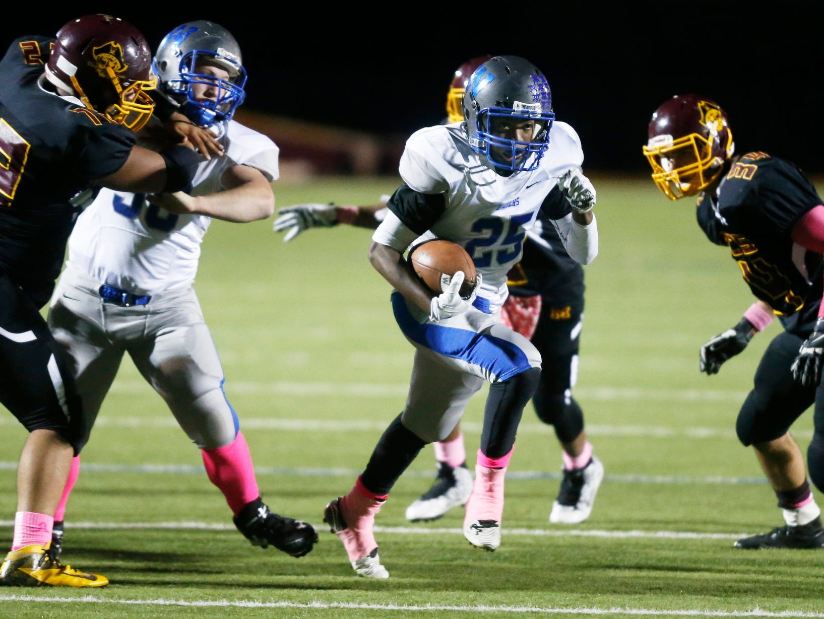 Woodbridge running back Kirby Williams gets through the line - helped by teammate Nikko Lucke (left) on his late 22-yard touchdown run for the go-ahead score in the fourth quarter of the Blue Raiders' 17-14 win at Milford High School.