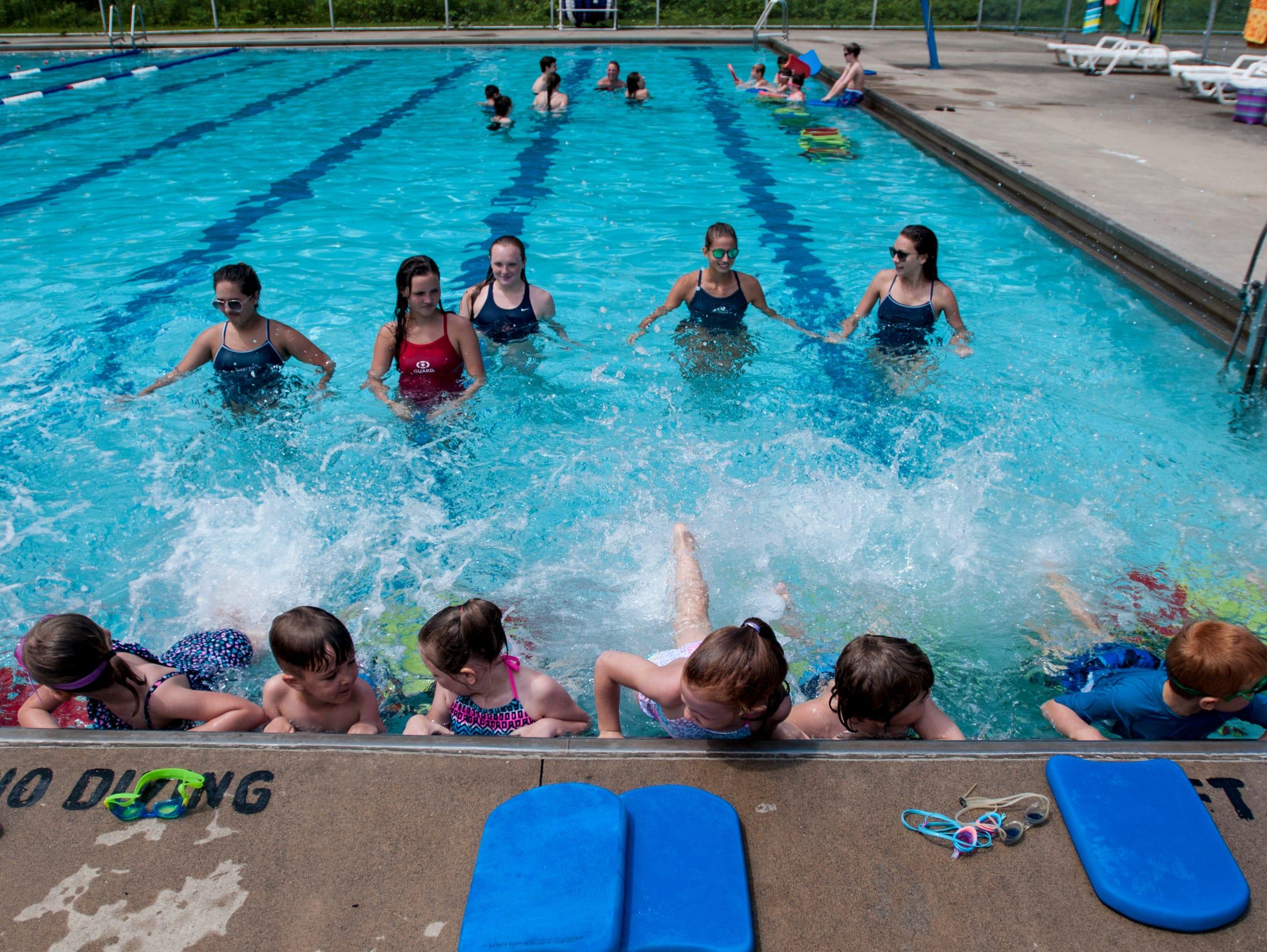 More than a dozen children participate in swim lessons