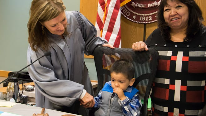 Judge Marci Beyer congratulates Jeremiah Gonzales and his mother Elizabeth on the finalization of his adoption on National Adoption Day. The ceremony was held on Monday, Nov. 21, 2016, at the 3rd Judicial District Courthouse.