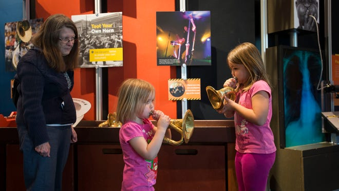 Paige, 3, and sister Elena Gliva, 6, play at an exhibit while their grandmother Opal Dick looks on, Wednesday, March 14, 2018, at the Fort Collins Museum of Discovery in Fort Collins, Colo.