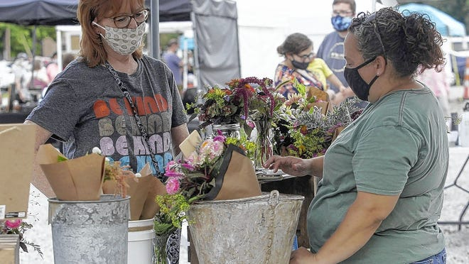 Roxi Beisel of Pickerington buys flowers from Evelyn Chamberlin, owner of Martha Jane's Flower Farm, while at the Olde Pickerington Farmers' Market on Sept. 10.