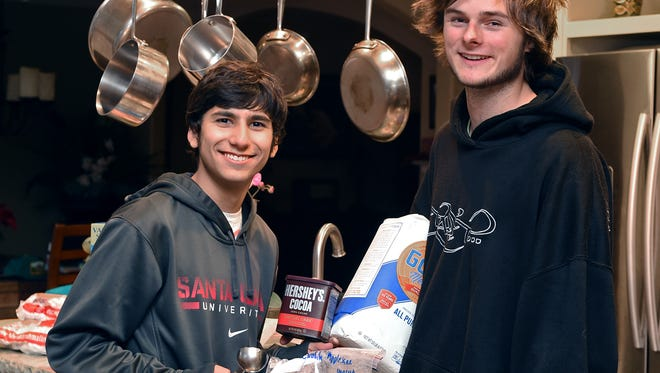 Longtime friends Cyrus Moassessi, 18, left, and Kienan Herman, 19, shown here in 2014, set up a charity coffee stand annually during the holidays. In 2016, the stand is in its 13th year.