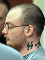 Anthony Baumgartner,  charged with the murder and dismemberment of Daniel Delfin, sits in Boone District Court for a preliminary hearing in 2013.  Baumgartner has a SS lightning bolt tattoo on his neck. The Nazis believed it represented victory.