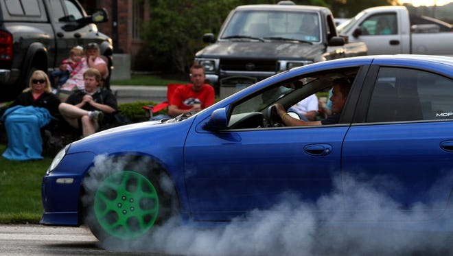 A driver spins a car's tires during the 2012 Super Cruise on Hebron Road in Heath.