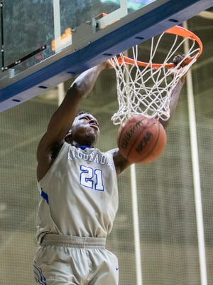 Darryl Tucker (21) grabs the rim after slam dunking the ball during the men's basketball game against Shorter University at the University of West Florida on Saturday, February 25, 2017.